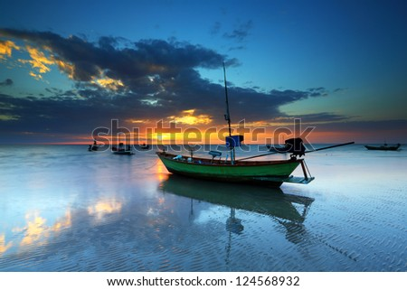 Fishing boats parked on a sandy beach at sunset - stock photo