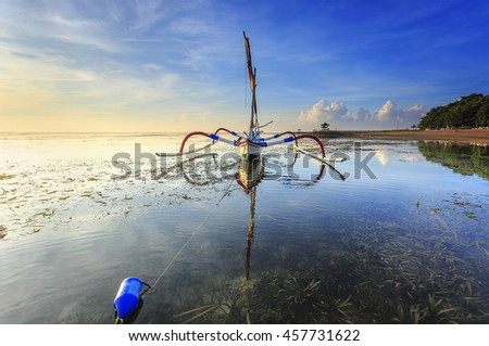 Fishing boats populate the shoreline at the Sanur Beach, Bali, Indonesia - stock photo