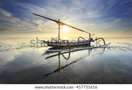 Fishing boats populate the shoreline at the Sanur Beach, bali, indonesia with flare sunlight - stock photo
