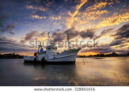 Fishing boats seaside  beach during sunset focus on the boat the front foreground. - stock photo