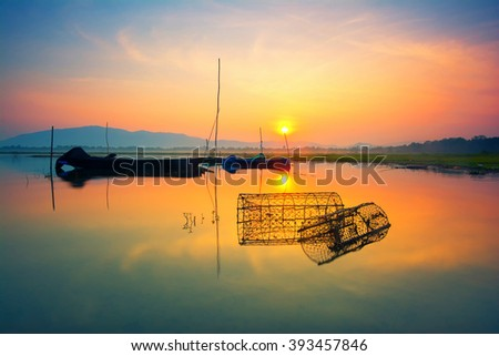 Fishing boats with morning sun on the sea and sunset. - stock photo
