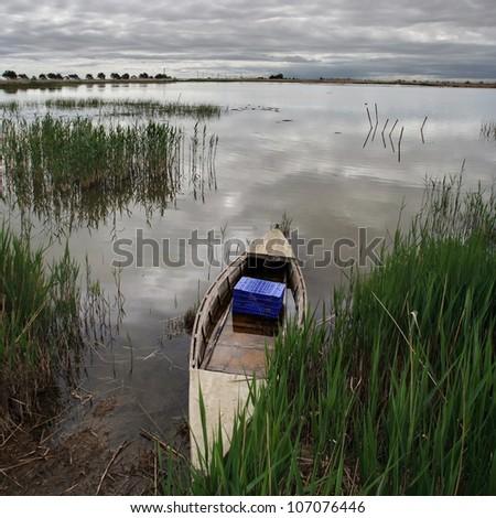 Fishing canoe on the shore of a lagoon. - stock photo