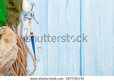 Fishing equipment on blue wooden table. Top view with copy space - stock photo
