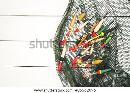 Fishing floats are located on grid nets for catching fish on a wooden surface in white - stock photo