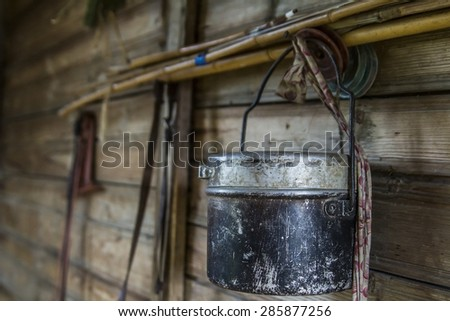 fishing gear and fishing rods bowler in the village on the wall of the shed - stock photo