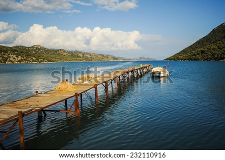 fishing harbor with boat and pier - stock photo