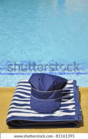 fishing hat and striped towel in the pool
