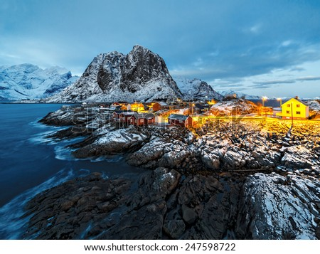 Fishing hut (rorbu) and towering mountain peaks at sunset - Reine, Lofoten islands, Norway - stock photo