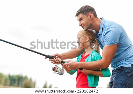Fishing is fun. Cheerful father and daughter fishing together and smiling - stock photo