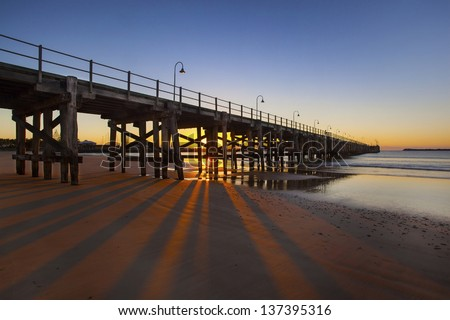 Fishing jetty at first light against morning sky - stock photo