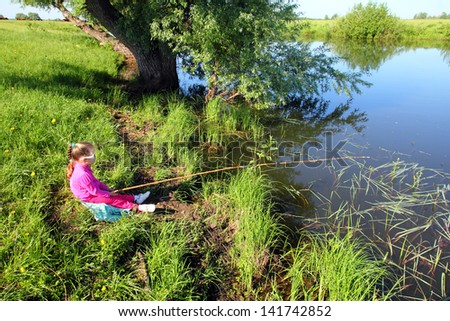 fishing littlle girl with rod on pond coast