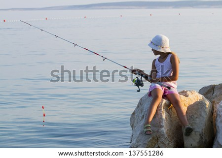 Fishing - lovely girl fishing on the beach - stock photo