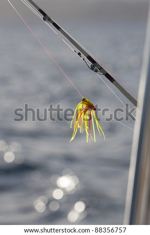 Fishing lure hangs off the side of a boat with the sun's reflection off of Caribbean waters. - stock photo