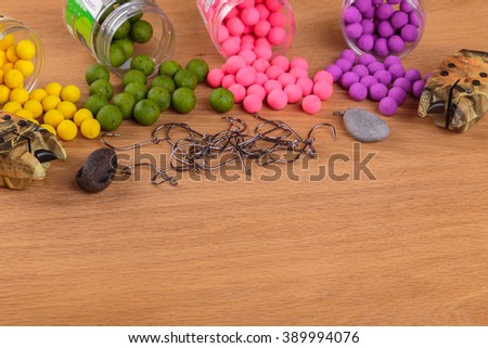 Fishing lure on a wooden table. Fishing tackle, baits, floats, feeders. - stock photo