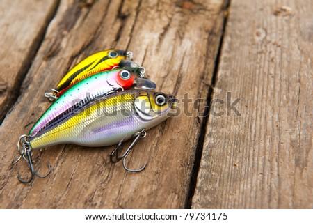 Fishing lures on old wooden bridge - stock photo