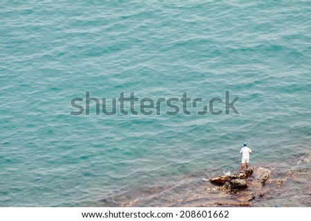 Fishing man in front of the ocean - stock photo