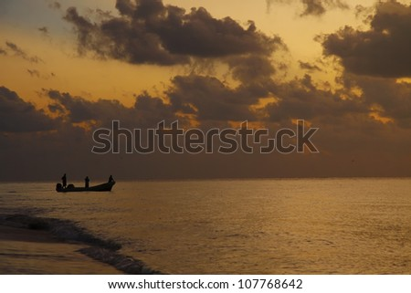 Fishing men on a boat at sunset - stock photo