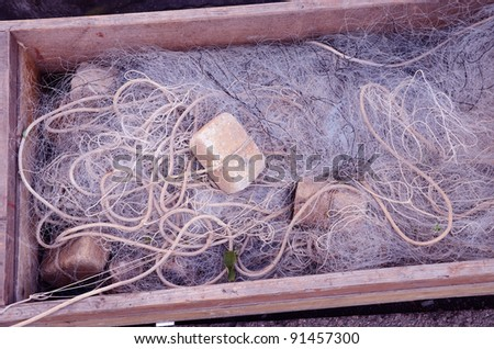 Fishing net in wooden box. Tool for fishing. Illegal fishing. - stock photo