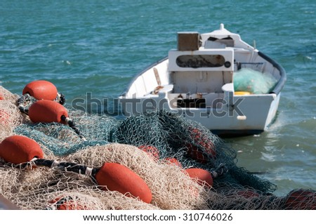 Fishing nets are on the boat moorage ready for loading at fishing boat - stock photo