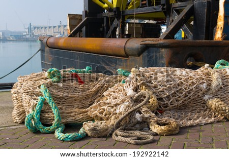 fishing nets in front of a fishing trawler in the scheveningen harbor in the netherlands - stock photo
