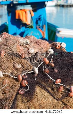 Fishing nets with ropes and floats in the harbor, in the background, blurred fishing boats - stock photo
