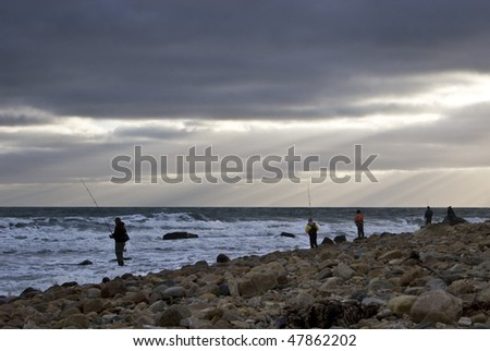 Fishing off the Atlantic Ocean seashore at Montauk Point, Long Island. Sun rays streaming trough an opening of the clouds - stock photo