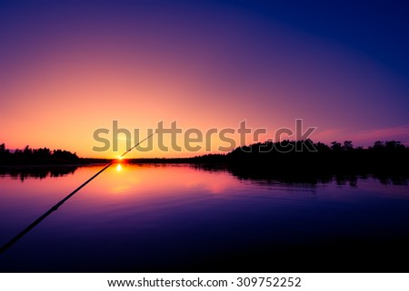 Fishing on a forest lake at sunset. View from the boat, image vignetting and soft orange-purple toning - stock photo