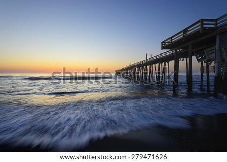 Fishing Pier and Ocean Waves at Sunrise - stock photo