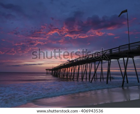 Fishing pier on the Outer Banks of North Carolina as the sun begins to rise. - stock photo
