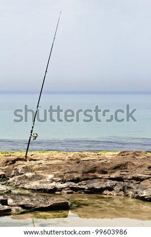 fishing pole on a rocky beach - stock photo