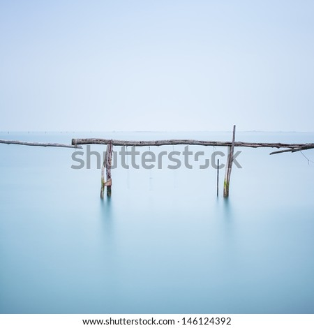 Fishing poles for clams and mussels and soft water on a quiet water landscape. Long exposure photography - stock photo