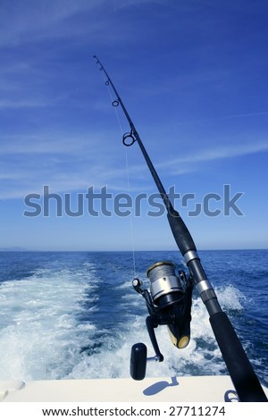 Fishing rod and reel on a boat, vacation on blue sea and summer sky - stock photo