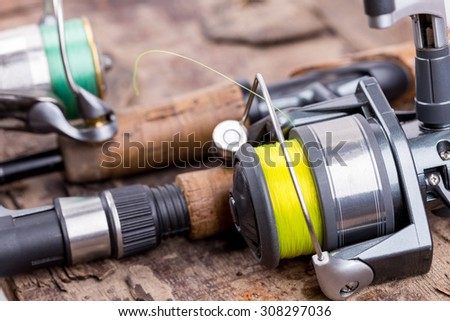 fishing rod and reel with line on natural background for frame, print, design - stock photo