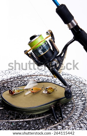 Fishing rod and reel with plastic baits on white background. Different kinds of the plastic baits on the bag for baits. - stock photo
