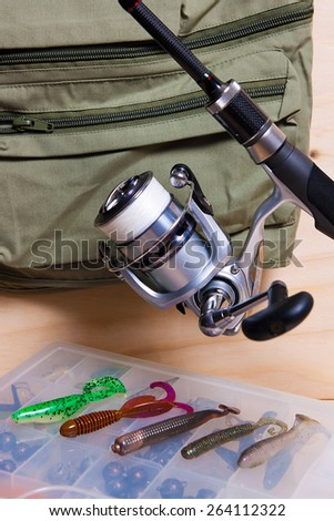 Fishing rod and reel with silicone baits. Fishing silicone lures on the box. - stock photo