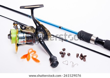 Fishing rod and reel with silicone baits on white. Fishing silicone lures. - stock photo