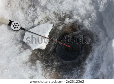 Fishing rod for Ice fishing on the background of the holes  - stock photo