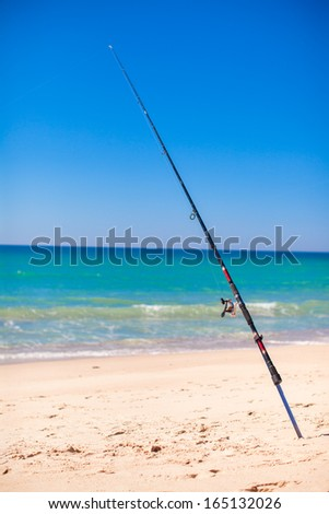 Fishing rod in white sand on tropical beach - stock photo