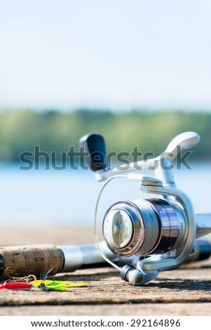 fishing rod on jetty close to lake - stock photo