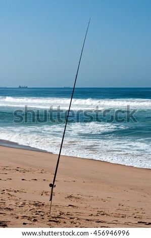 Fishing rod on the beach with ships on the horizon. - stock photo
