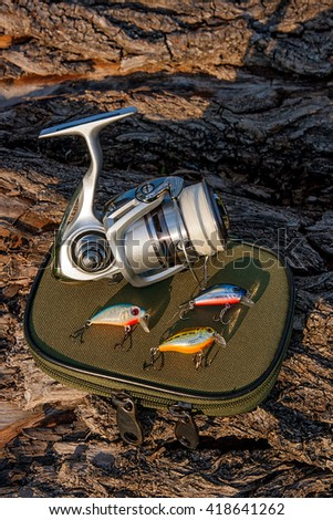 Fishing rod with fishing reel on the natural background. Assorted of various kind of fishing plastic baits. Objects on the green box for fishing bait on the old tree with brown bark. - stock photo