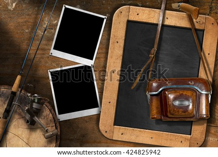 Fishing rod with reel, vintage camera with leather case, two empty instant photo frames and a blank blackboard on a wooden wall - stock photo