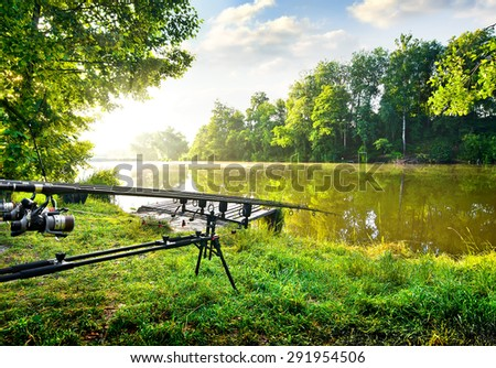 Fishing rods near calm river in the morning - stock photo