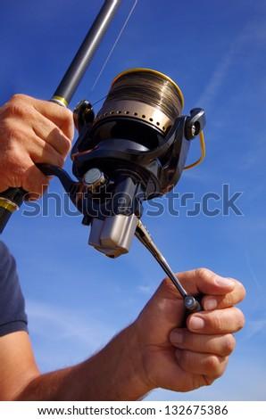 Fishing scene. Close-up on fishing reel - stock photo