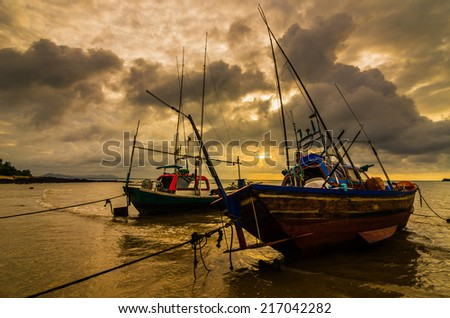Fishing sea boat and Sunrise clouds before strom in Thailand gold light tone - stock photo
