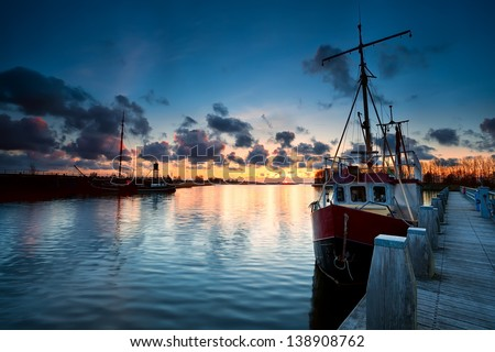 fishing ships at sunset in Zoutkamp, Netherlands - stock photo