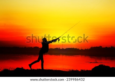 Fishing silhouette at the lake on sunset - stock photo