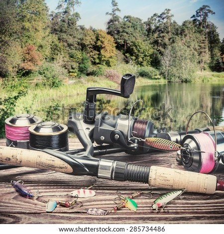 fishing tackle and accessories on the table autumn day. Focus on spinning. toned image - stock photo