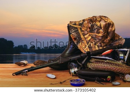 Fishing tackle and sunset - stock photo