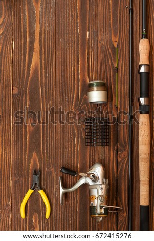 Fishing tackle - fishing spinning, spools and lures on dark wooden background.Top view with copyspace